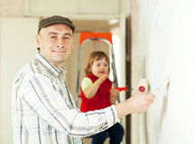 Man with child paints wall Stock Images