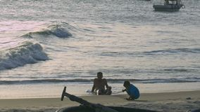 Man and Child Play on Beach against Evening Sun. NHA TRANG/VIETNAM - NOVEMBER 07 2017: Man and child play at waterline on wet sand beach against wide rolling stock video footage