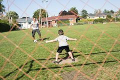Man with child playing football on field Royalty Free Stock Photography