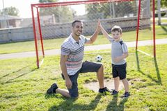 Man with child playing football on field Royalty Free Stock Image
