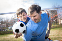 Man with  child playing football on  pitch. A man with with child playing football on football pitch Stock Image