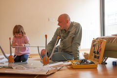 Man with child repairing coffee table royalty free stock photo