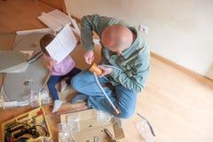 Man with child repairing furniture royalty free stock image