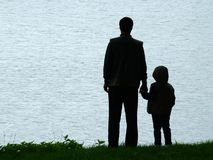 Man and child silhouette at evening. Man and child silhouette at lakeside in evening Royalty Free Stock Photography