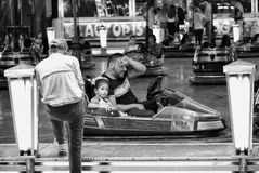 Man and child take a break from driving a dodgem car at the fair. Stock Images