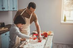 Dad and boy doing cookies with molds. Man and child working with knead in kitchen. They cutting figurines from the dough. Copy space in right side Stock Image