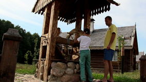 Man with children are bucket of water from the well in the Russian village stock video footage