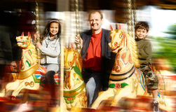 Man with children enjoying fairground ride stock image