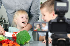 Man with children filming the meal preparation. Home Video Camera, Blogging, Cooking, Domestic Kitchen.  Stock Photo