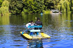A man with 2 children, Hasidic Jews, ride a catamaran on a lake in the autumn Sofia park in Uman, Ukraine royalty free stock image