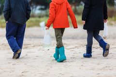 Man and children walking at the beach. Man and children walking in rainwear at the beach stock photography
