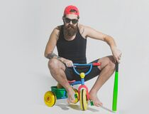 Man on a childrens bicycle. Bicycle rider, bearded angry man holds green baseball bat on bicycle toy.