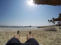 Man chilling at beach legs and foot in Oman Salalah Souly Bay royalty free stock photography