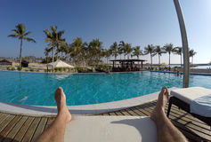 Man chilling at pool legs and foot in Oman Salalah Souly Bay Stock Photos