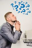 Man with chin on hands thoughtfully looking upwards. On question marks sitting at table with laptop in office Royalty Free Stock Images