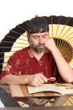 Man in chinese costume reads Stock Photos