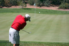 Man chipping ball onto green. Man successfully chipping golf ball onto green, focus on golfer Royalty Free Stock Images