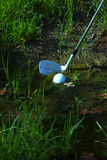Man chipping ball from water hazard Stock Photo