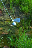 Man chipping ball from water hazard royalty free stock photography