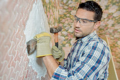 Man chipping tiles off wall Stock Photo