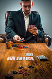The man, chips for gamblings, drink and playing cards Royalty Free Stock Photos