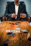The man, chips for gamblings, drink and playing cards Royalty Free Stock Images