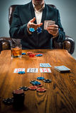 The man, chips for gamblings, drink and playing cards Stock Photos