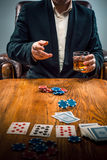 The man, chips for gamblings, drink and playing cards Stock Photo