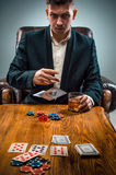 The man, chips for gamblings, drink and playing cards Stock Photography