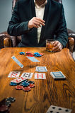 The man, chips for gamblings, drink and playing cards Royalty Free Stock Image