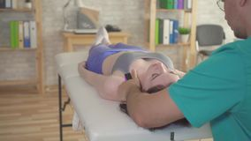 Man chiropractor relieves neck pain in a young woman stock video footage