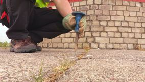 Man with chisel deepens crack close up. In summer day stock footage