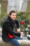 Man with chocolates and a rose being stood up Royalty Free Stock Photography