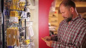 Man choose some things at the yacht centre. Caucasian man choosing some things at the yacht centre. Bearded man dressed in checkered shirt standing near the shop stock footage