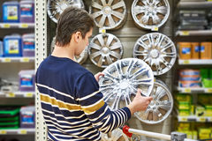 Man chooses alloy wheels for car wheels in supermarket Royalty Free Stock Photography
