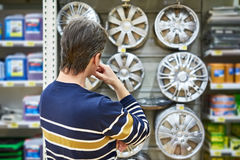 Man chooses alloy wheels for your car wheels in supermarket Royalty Free Stock Images