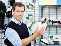 Man chooses ball for rugby in sports shop. Man chooses ball for rugby in the sports shop stock images