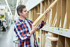 Man chooses baluster for stairs. Man chooses wooden baluster for stairs stock images