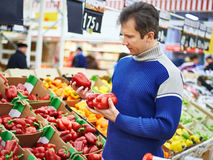 Man chooses bell peppers in store Stock Photo