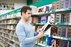Man chooses book in store Stock Photography