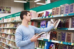 Man chooses book in store Royalty Free Stock Images