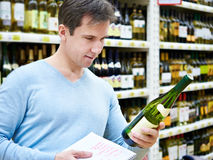 Man chooses bottle of white wine for date in shop Stock Image
