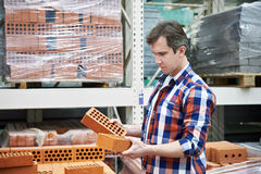 Man chooses building brick in store Royalty Free Stock Image