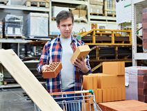 Man chooses and buys bricks in store Royalty Free Stock Photo