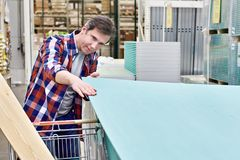 Man chooses and buys drywall in store Stock Photography