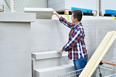 Man chooses and buys foam concrete bricks in store Stock Image