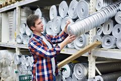 Man chooses and buys heat foil insulation in store Royalty Free Stock Photos