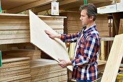 Man chooses plywood boards in store Royalty Free Stock Photography