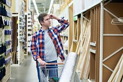 Man chooses and buys wooden board in store Royalty Free Stock Photo