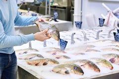 Man chooses carp fish in supermarket Royalty Free Stock Photography